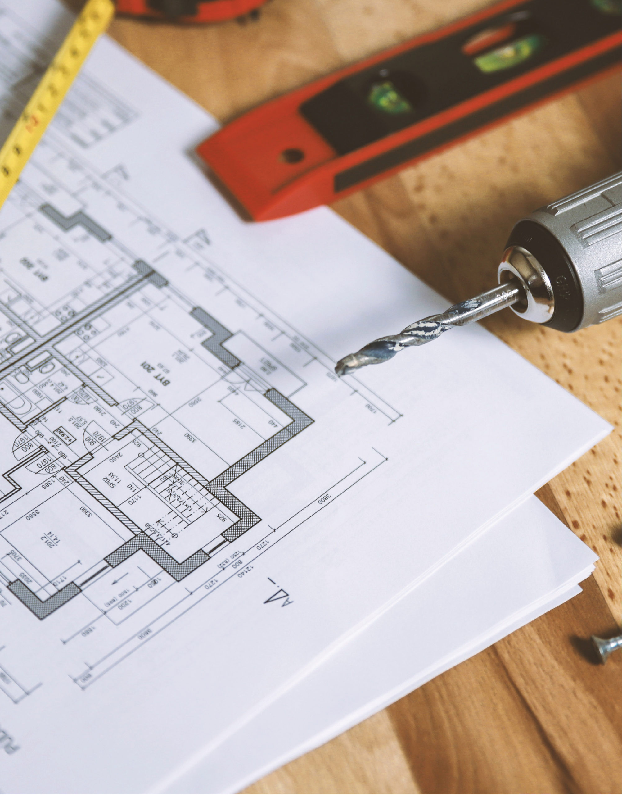 Photo featuring a drill, level, and tape measurer laid on top of blueprints.