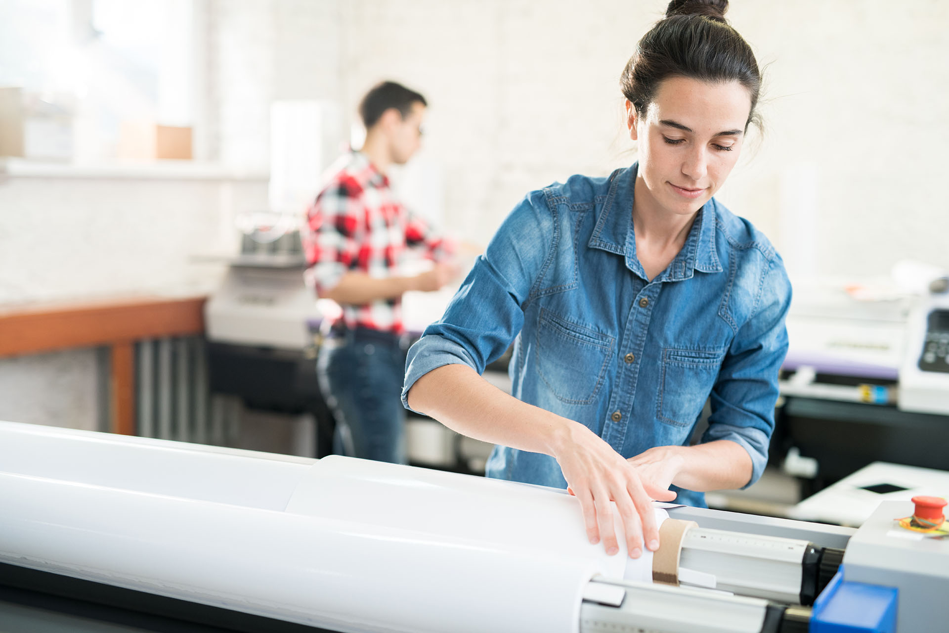 Serious confident young woman with hair bun loading wide format printer while working at printing house